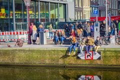 AMSTERDAM NEDERLÄNDERNA, MARS, 10 2018: Utomhus- sikt av oidentifierat folk som sitter i en flodstrand av kanalen som tycker om Royaltyfri Fotografi