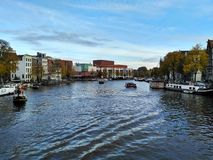 Amsterdam/Nederländerna - Oktober 30 2016: Sikt på den Amsterdam kanalen, central operahus i avståndet arkivbild