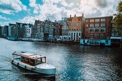 Amsterdam Nederländerna som dansar hus över den flodAmstel gränsmärket i gammalt europeiskt stadslandskap Pittoreska moln på fotografering för bildbyråer
