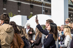 Amsterdam, Nederland - April 31, 2017: Aziatische dame die selfies terwijl mensen die in de straten rondwandelen nemen Royalty-vrije Stock Foto's
