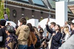 Amsterdam, Nederland - April 31, 2017: Aziatische dame die selfies terwijl mensen die in de straten rondwandelen nemen Stock Fotografie