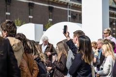 Amsterdam, Nederland - April 31, 2017: Aziatische dame die selfies terwijl mensen die in de straten rondwandelen nemen Stock Foto