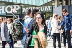 Amsterdam, Nederland - April 31, 2017: Aziatische dame die selfies terwijl mensen die in de straten rondwandelen nemen Stock Afbeeldingen