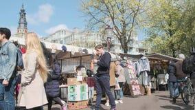 Amsterdam/Nederland - April 2019: Bezoekers en markttribunes bij Waterloo markt in Amsterdam, Nederland stock footage