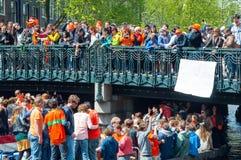 AMSTERDAM, 27 NEDERLAND-APRIL: Boot paty op het Singel-kanaal, menigte van mensen op de brug op de Dag van de Koning op 27,2015 A Royalty-vrije Stock Fotografie