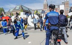 Amsterdam, Nederland - April 31, 2017: De handhaving politieafdeling die een blik hebben de straatprestaties Royalty-vrije Stock Afbeeldingen