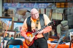 AMSTERDAM, 27 NEDERLAND-APRIL: De straatmusicus speelt de gitaar tijdens de Dag van de Koning op 27,2015 April Stock Afbeeldingen