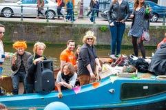 AMSTERDAM, 27 NEDERLAND-APRIL: De vrolijke plaatselijke bewoners en de toeristen in sinaasappel hebben pret op een boot tijdens d Stock Fotografie