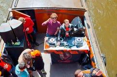 AMSTERDAM, 27 NEDERLAND-APRIL: DJ speelt muziek op bootpartij op het kanaal van Amsterdam tijdens de Dag van de Koning op 27,2015 Stock Foto's