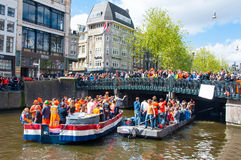 AMSTERDAM, 27 NEDERLAND-APRIL: Mensen op Partijboot met menigte van mensen op de brug op de Dag van de Koning op 27,2015 April Stock Fotografie