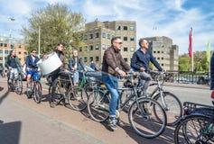Amsterdam, Nederland - April 31, 2017: Mensen van Amsterdam die hun fietsen op een dagelijkse basis met behulp van met inbegrip v royalty-vrije stock afbeeldingen