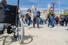 Amsterdam, Nederland - April 31, 2017 - Rolstoel die zich in het midden van de menigte op museumplein in Amsterdam bevinden stock fotografie