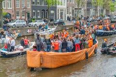 Amsterdam, Nederland, 27 April 2018, Toeristen en plaatselijke bewoners s stock afbeelding