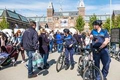 Amsterdam, Nederland - April 31, 2017: Vriendschappelijke dame van de handhaving politie die hoogte vijf geven aan weinig jongen Stock Foto's