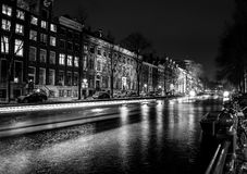 AMSTERDAM, NEDERLAND - DECEMBER 14, 2015: Zwart-witte foto die van cruiseboot zich op nachtkanalen bewegen van Amsterdam stock afbeelding