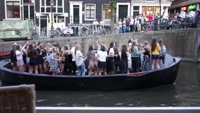 Amsterdam, Nederland - Juni 14, 2017: De groep jonge vrolijke meisjes maakt gang door de boot op kanalen van Amsterdam stock videobeelden