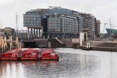 AMSTERDAM, NEDERLAND - JUNI 25, 2017: Toeristenboten op de achtergrond van moderne hotel Dubbele Boom door Hilton Stock Foto
