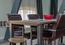 AMSTERDAM, NEDERLAND - Mei 2019: Hout en metaaleettafel met comfortabele leerstoelen, houten rode kom en open tijdschrift in a stock fotografie