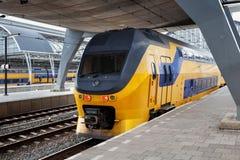 AMSTERDAM, NETHERLAND - CZERWIEC 25, 2017: Żółty holendera pociąg na Amsterdam Centraal staci platformie w ranku Zdjęcie Royalty Free