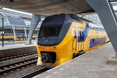 AMSTERDAM, NETHERLAND - JUNE 25, 2017: Yellow Dutch train on the Amsterdam Centraal station platform in morning. Centraal is the largest railway station of Royalty Free Stock Photo