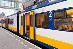 AMSTERDAM, NETHERLAND - 25 JUNI, 2017: Gele Nederlandse trein op het de postplatform van Amsterdam Centraal in ochtend Royalty-vrije Stock Fotografie