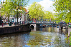 AMSTERDAM,NETHERLANDS-APRIL 27: Amsterdam canal with bikes along the bridge on King's Day in Amsterdam, the Netherlands. Royalty Free Stock Images
