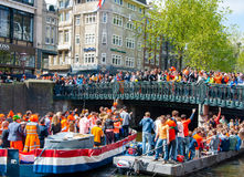 AMSTERDAM,NETHERLANDS-APRIL 27: Boat paty on the Singel canal, crowd of people on the bridge on King's Day on April 27,2015. Royalty Free Stock Photography