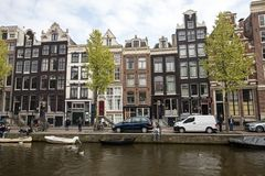 Canal scene with a bicycles, boats and traditional Dutch houses in Red Light District. Amsterdam, Netherlands - April 20, 2017: Canal scene with a bicycles stock photos