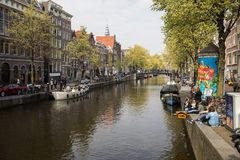 Canal scene with a bicycles, boats and traditional Dutch houses in Red Light District. Amsterdam. Netherlands. Amsterdam, Netherlands - April 20, 2017: Canal stock photos