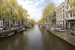 Canal scene with a bicycles, boats and traditional Dutch houses in Red Light District. Amsterdam. Netherlands. Amsterdam, Netherlands - April 20, 2017: Canal royalty free stock photo