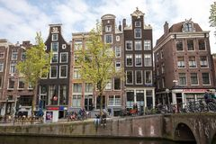 Canal scene with a bicycles and traditional Dutch houses in Red Light District. Amsterdam. Netherlands. Amsterdam, Netherlands - April 20, 2017: Canal scene with stock photography