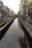 Canal  scene with a bicycles and traditional Dutch houses in Red Light District. Amsterdam. Netherlands. Amsterdam, Netherlands - April 20, 2017: Canal  scene royalty free stock image