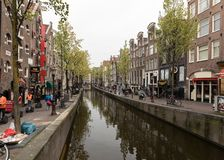Canal scene with traditional Dutch houses in Red Light District. Amsterdam. Netherlands. Amsterdam, Netherlands - April 20, 2017: Canal scene with traditional royalty free stock photo