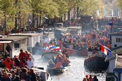 Amsterdam. The Netherlands - April 30, 2013 : Celebration of queensday on a  canal with houseboats Royalty Free Stock Photos