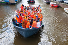 AMSTERDAM,NETHERLANDS-APRIL 27:  Crowd of local people dressed in orange celebrate King's Day in a boat on April 27,2015. Royalty Free Stock Photography
