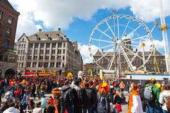 AMSTERDAM,NETHERLANDS-APRIL 27: Dam Square full of locals and tourists dressed in orange on King's Day on April 27,2015, Amsterdam Royalty Free Stock Photos