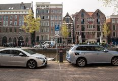 Electric vehicles plugged into charging points on a road in Amsterdam. Amsterdam, Netherlands - April 20, 2017: Electric vehicles plugged into charging points on royalty free stock images