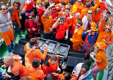 AMSTERDAM,NETHERLANDS-APRIL 27:  People in orange clothes during King's Day on a boat on April 27,2015 in Amsterdam. Royalty Free Stock Photo
