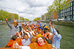 AMSTERDAM, NETHERLANDS - APRIL 30: People in orange cruising thr Stock Photography