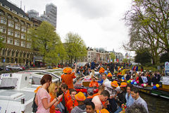 AMSTERDAM, NETHERLANDS - APRIL 30: People in orange cruising thr Stock Images