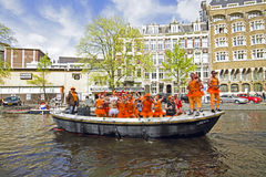 AMSTERDAM, NETHERLANDS - APRIL 30: People in orange cruising thr Royalty Free Stock Photos