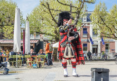 Amsterdam , Netherlands - April 31, 2017 : Scottish bagpiper tuning his instrument in the streets of Amsterdam wearing Stock Photo