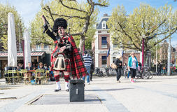 Amsterdam , Netherlands - April 31, 2017 : Scottish bagpiper tuning his instrument in the streets of Amsterdam wearing Royalty Free Stock Photo