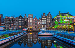 AMSTERDAM, NETHERLANDS - APRIL 3, 2008: Tour boats and dancing h. Ouses along the Damrak canal illuminated by night light Stock Photography