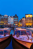 AMSTERDAM, NETHERLANDS - APRIL 3, 2008: Tour boats and dancing h. Ouses along the Damrak canal illuminated by night light Stock Photo
