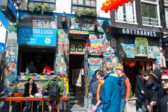 AMSTERDAM,NETHERLANDS-APRIL 27: Tourists go by Bulldog coffeeshop in red-light district on King's Day on April 27,2015. Royalty Free Stock Images