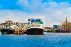 AMSTERDAM, NETHERLANDS, APRIL, 23 2018: View of many boats in the shore of canals, is the capital and most populous city Stock Image