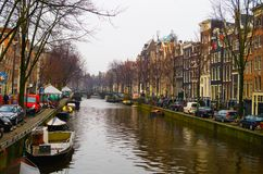 AMSTERDAM, NETHERLANDS, APRIL, 23 2018: View of some cars parked in the street close to many boats in the canals of. Amsterdam, is the capital and most populous Royalty Free Stock Photo
