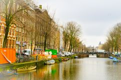 AMSTERDAM, NETHERLANDS, APRIL, 23 2018: View of some cars parked in the street close to many boats in the canals of. Amsterdam, is the capital and most populous Stock Photography