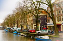 AMSTERDAM, NETHERLANDS, APRIL, 23 2018: View of some cars parked in the street close to many boats in the canals of. Amsterdam, is the capital and most populous stock images